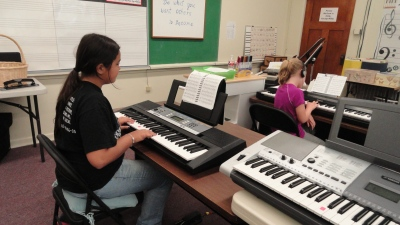 Camila learning to play on her class keyboard ~ Older Children's Beginning Piano Class